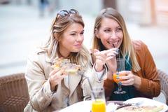 Portrait de deux jeunes femmes meating en café mangeant de la pizza dehors Photographie stock