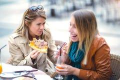 Portrait de deux jeunes femmes meating en café mangeant de la pizza dehors Photo libre de droits