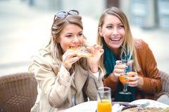 Portrait de deux jeunes femmes meating en café mangeant de la pizza extérieure Photos libres de droits
