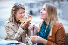 Portrait de deux jeunes femmes meating en café mangeant de la pizza extérieure Photos stock