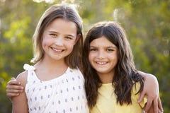 Portrait de deux jeunes filles heureuses embrassant dehors Image stock