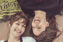 Portrait de deux jeunes filles souriant sur la plage Photographie stock libre de droits