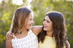 Portrait de deux jeunes filles de sourire regardant l'un l'autre dehors Photographie stock
