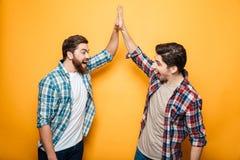 Portrait de deux jeunes hommes heureux donnant la haute cinq Photo stock