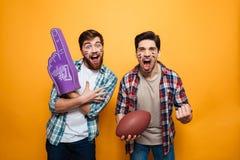 Portrait de deux jeunes hommes heureux tenant la boule de rugby photographie stock