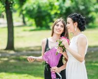 Portrait de deux jeunes jolis amis de femmes parlant en parc vert d'été Jolies femelles jeune mariée et demoiselle d'honneur sour Photographie stock libre de droits