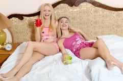 Portrait de deux jolies amies sexy ayant le thé potable d'amusement tenant les tasses rouges et vertes et regardant l'appareil-ph Photographie stock