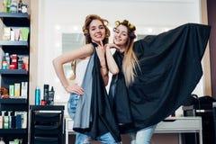 Portrait de deux jolies blondes utilisant des rouleaux de cheveux et de cap se tenant dans la pose idiote drôle regardant in came Image libre de droits
