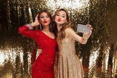 Portrait de deux jolies jeunes femmes dans des robes scintillantes Images stock