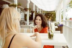 Portrait de deux jolis amis dans le boire de café et parler intérieurs Photographie stock