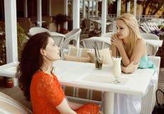 Portrait de deux jolis amis en café buvant et parlant Image libre de droits