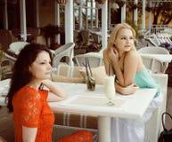 Portrait de deux jolis amis en café buvant et parlant Photographie stock libre de droits