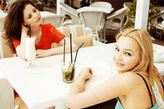 Portrait de deux jolis amis en café buvant et parlant Photo libre de droits