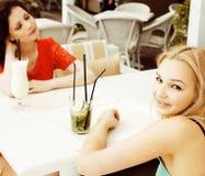 Portrait de deux jolis amis en café buvant et parlant Images stock