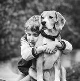 Portrait de deux meilleurs amis - le petit garçon étreint le chien de briquet Photos stock