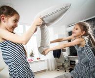 Portrait de deux petites soeurs combattant avec des oreillers Photo stock