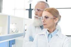 Portrait de deux scientifiques dans l'uniforme et lunettes semblant parties et pose photo stock