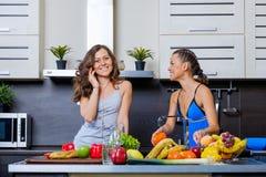 Portrait de deux soeurs jumelles ayant l'amusement le matin préparant le petit déjeuner Photo libre de droits