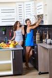 Portrait de deux soeurs jumelles ayant l'amusement le matin préparant le petit déjeuner Images stock