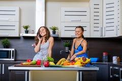 Portrait de deux soeurs jumelles ayant l'amusement le matin préparant le petit déjeuner Image libre de droits