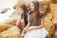 Portrait de deux soeurs mignonnes s'asseyant sur la plage Photo libre de droits