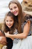 Portrait de deux soeurs mignonnes s'asseyant sur la plage Photographie stock