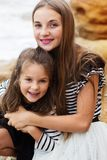 Portrait de deux soeurs mignonnes s'asseyant sur la plage Photo stock