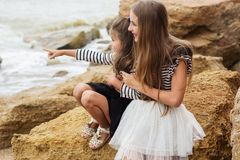 Portrait de deux soeurs mignonnes s'asseyant sur la plage Images libres de droits