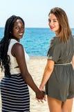Portrait de diversité de deux filles de l'adolescence tenant des mains Images stock