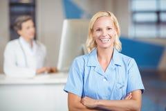 Portrait de docteur assez féminin avec des bras croisés Image stock