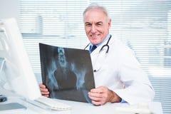 Portrait de docteur avec le rayon X se reposant devant l'ordinateur Photo libre de droits