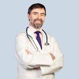 Portrait de docteur d'une cinquantaine d'années heureux avec le stéthoscope. sur un pâle Photo libre de droits