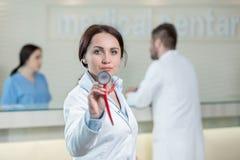 Portrait de docteur de femme au couloir d'hôpital, regardant l'appareil-photo Photo stock