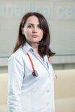 Portrait de docteur de femme au couloir d'hôpital, regardant l'appareil-photo Photographie stock libre de droits