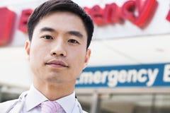 Portrait de docteur de sourire en dehors de l'hôpital, connexion de chambre de secours le fond, plan rapproché images libres de droits