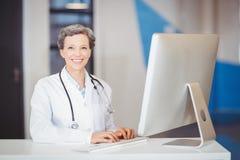 Portrait de docteur de sourire travaillant au bureau d'ordinateur Photo libre de droits