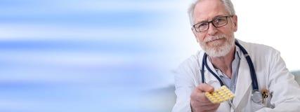 Portrait de docteur donnant des pilules Photos stock
