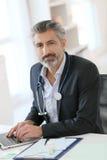 Portrait de docteur expérimenté au bureau Photographie stock