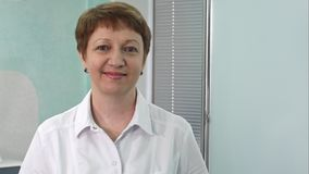 Portrait de docteur féminin âgé sur le couloir d'hôpital regardant le sourire d'appareil-photo Photo libre de droits