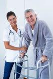 Portrait de docteur féminin aidant l'homme supérieur à marcher avec le marcheur Photos stock