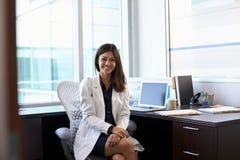 Portrait de docteur féminin Wearing White Coat dans le bureau Images stock