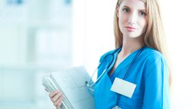 Portrait de docteur de femme avec le dossier au couloir d'hôpital Photographie stock
