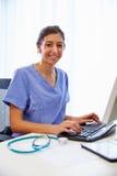 Portrait de docteur féminin In Office Working à l'ordinateur Photographie stock libre de droits