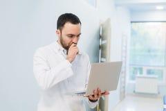 Portrait de docteur gai se reposant au bureau travaillant à l'ordinateur portable Photographie stock