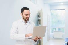 Portrait de docteur gai se reposant au bureau travaillant à l'ordinateur portable Images libres de droits