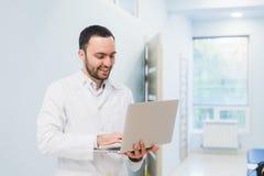 Portrait de docteur gai se reposant au bureau travaillant à l'ordinateur portable Photo libre de droits