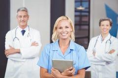 Portrait de docteur gai tenant le comprimé numérique tandis que les collègues avec des bras croisaient photo stock