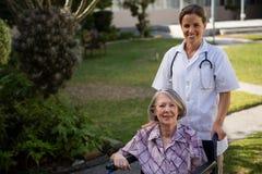 Portrait de docteur se tenant prêt la femme supérieure s'asseyant sur le fauteuil roulant Photo libre de droits