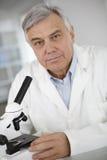Portrait de docteur supérieur regardant par le microscope Photo libre de droits
