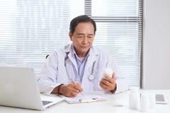Portrait de docteur supérieur se reposant à son bureau dans le bureau médical Photographie stock